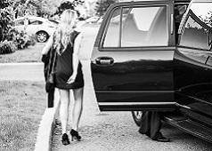 žena v spoločenských šatách na ples u auta